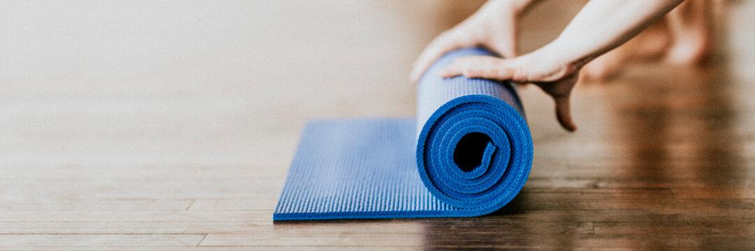 Yogi rolling her blue yoga mat