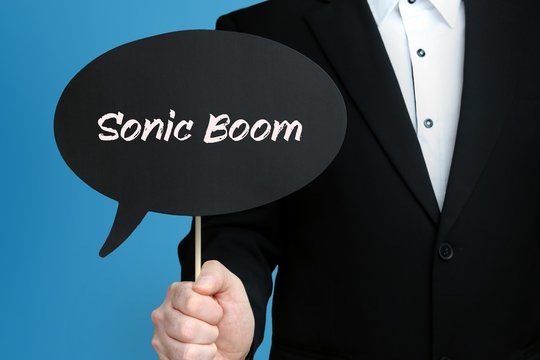 Sonic Boom. Businessman (Man) is holding the sign of speech bubble in his hand. Handwritten Text on the Label. Business, Finance, Analysis, Economy
