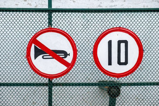 Road sign speed limit 10 km h and Beeping is prohibited on the green mesh fence.