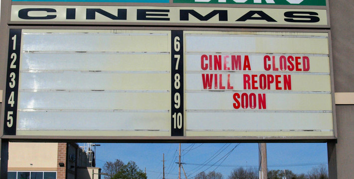 A sign for an American mall multiplex movie theater closed during the Covid-19 outbreak says Cinema Closed Will Reopen Soon in the Spring of 2020