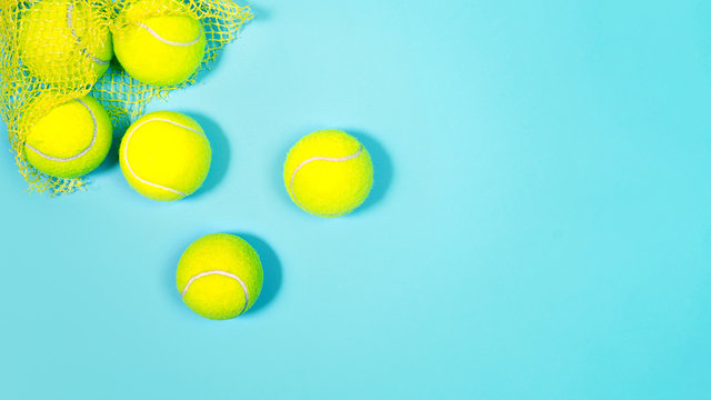 Sport layout with tennis balls close up on blue tennis court. Copy space, selective focus. Blue and yellow.