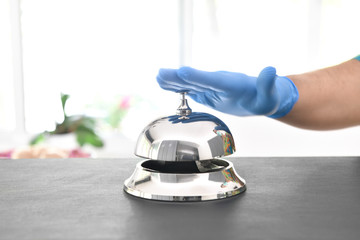 Coronavirus free tourism concept; customers ringing hotel bell using gloves at new normal