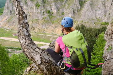 Woman high up on a via ferrata route called 'Spirala Mare' in Baia de Fier, Gorj county, Romania, gazes in the distance, sitting down next to a tree trunk.