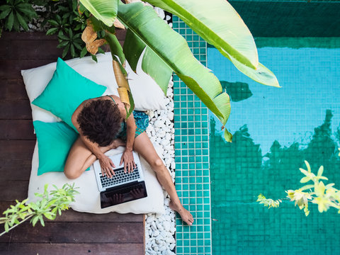 bird view of a remote online working digital nomad women with curly hair and laptop sitting crossed legged at a sunny turquoise water pool surrounded by cushions and plants in the foreground
