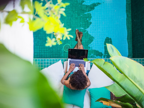 bird view of a remote online working digital nomad women with curly hair and laptop sitting at a sunny turquoise water pool having feet in the water surrounded by cushions and plants in the foreground