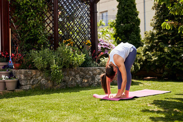 Young flexible caucasian girl standing on yoga mat and stretching her backs.