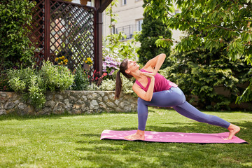 Young attractive brunette standing on the mat in her backyard in practicing yoga. Revolved Crescent Lunge yoga pose.