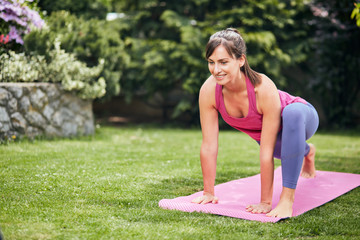 Young attractive yogi brunette in Lizard yoga posture. Backyard exterior.