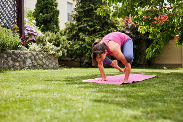 Young strong fit yogi brunette in Crane yoga posture. Backyard exterior.