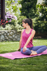 Young attractive brunette standing on the mat in her backyard in practicing yoga.