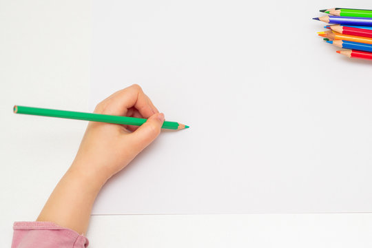 Top view of child's left hand drawing at blank white paper with a green pencil. Copy space for text. Mockup.