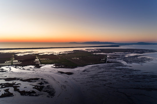 Aerial view of the Sado Estuary near the village of Carrasqueira, with a rice plantation, the Troia Peninsula and the Arrabida Mountain on the background at sunset, in Portugal.