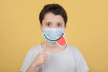 kid wearing medical mask and smile false on stick