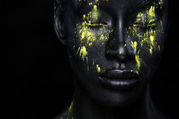 Woman with black body paint. Cheerful young african girl with art bodypaint. An amazing model with yellow makeup. Closeup face.