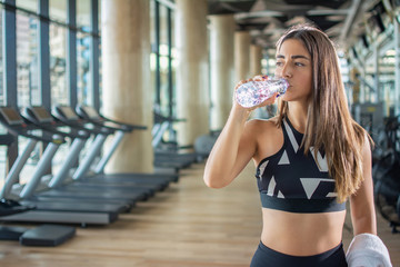 Beautiful young fit woman drinking water after training at gym.