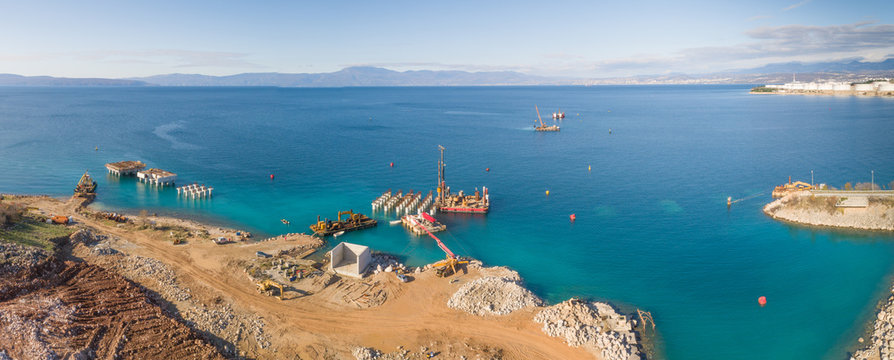 Panoramic aerial view of machinery on concrete platforms at the construction of future LNG terminal on the shore of the bay in Omisalj, Croatia