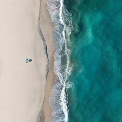 Aerial view of a lonely beach umbrella along the sea shore, Sant'Andrea Apostolo dello Ionio, Calabria, Italy.