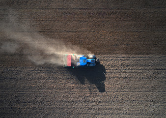 Aerial view of a blue and red tractor ploughing the earth, Rosasco, Lombardy, Italy.