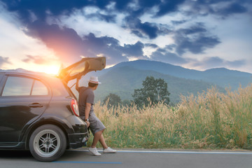 Man traveler sitting on hatchback black car with mountain view background in country road,Travel in holiday concept. Wall mural