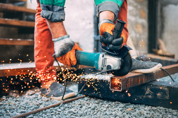 a man is sawing metal with an angle grinder.