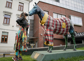 A woman, wearing protective face mask amid the outbreak of the coronavirus disease (COVID-19), poses for her friend next to a horse sculpture with a mask, in Moscow
