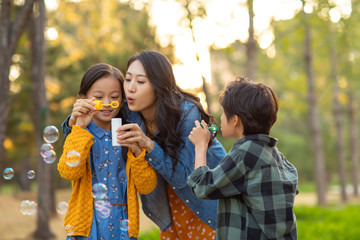 Happy young family blowing bubbles in park