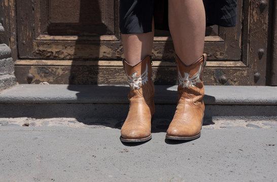Cowboy women boots in front of a rustic door