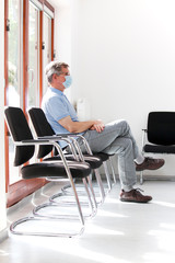 Patient or visitor with surgical mask sitting in a waiting room of a hospital or office