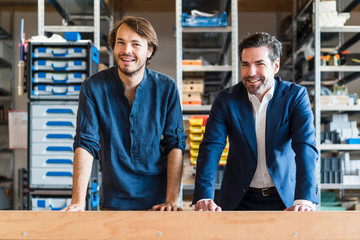 Portrait of smiling businessman and employee in factory