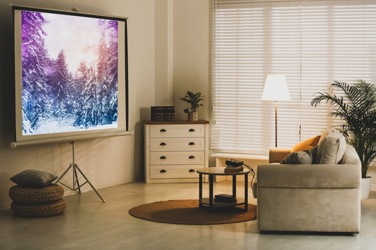 Stylish room with modern video projector and comfortable sofa