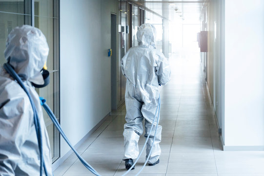 Cleaning staff desinfecting hospital against contageous virus, wearing protective clothing