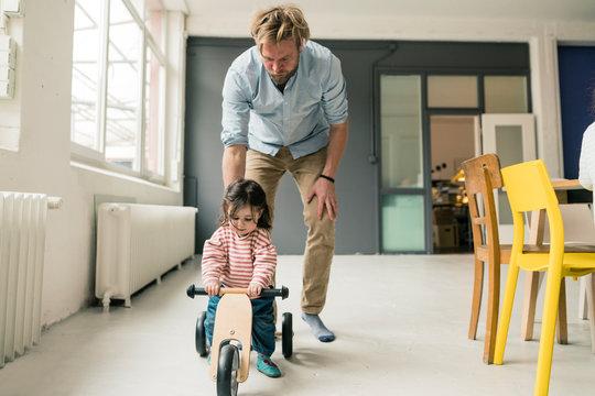 Father watching daughter using balance bicycle