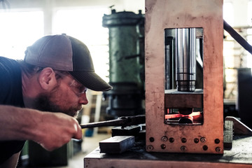 Knife maker working with damask steel at hydraulic sledge-hammer