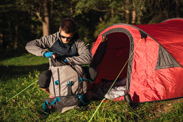 Man camping in Estonia, searching his backpack