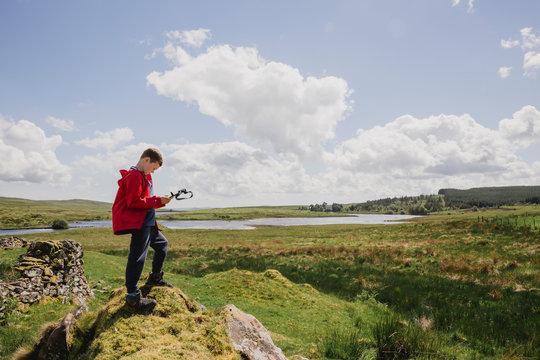 Boy looking at map, Cairngorms, Scotland, UK