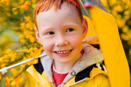 Portrait of redheaded little boy with umbrella