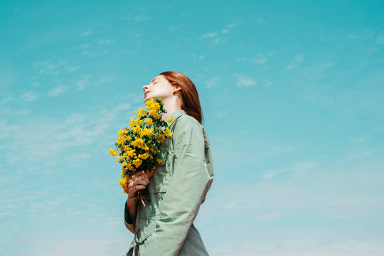 Redheaded young woman with eyes closed standing against sky holding bunch of yellow flowers