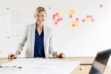Portrait of happy blond businesswoman in conference room with adhesive notes at whiteboard