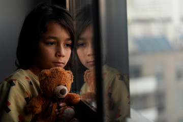 Boy with his teddy bear looking out of window at home