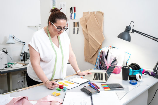 Seamstress drawing in front of a laptop working in tailor shop