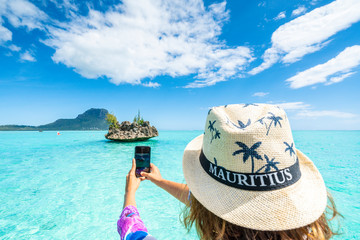 Woman photographing the tropical lagoon and Crystal Rock with smartphone, La Gaulette, Le Morne Brabant, Mauritius, Indian Ocean, Africa
