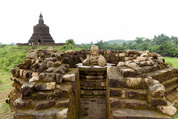 Zelfklevend Fotobehang Historisch mon. A ruined stone stupa with damaged Buddha statue in the centre, with West Myatazaung Pagoda in the background, Mrauk U, Rakhine, Myanmar (Burma), Asia