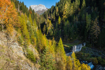 Autumn alpine Dolomites mountain view with small waterfall, Sudtirol, Italy