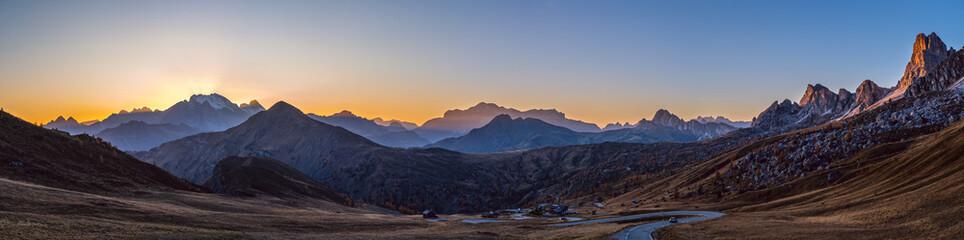 Sun glow in evening hazy sky. Mountain panoramic peaceful view from Giau Pass.