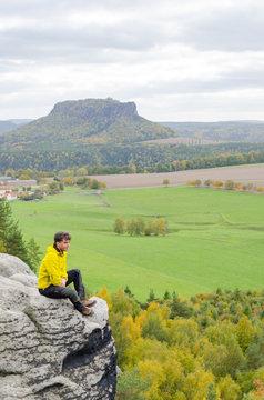 Deutschland, Sachsen, Sächsische Schweiz, Wanderung von Wehlen über die Rauensteine, Wanderer sitzt am Felsen über dem Abhang, Blick von den Rauensteinen auf den Lilienstein