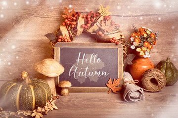 """Fall rustic decorations, text """"Hello Autumn"""" on a blackboard. Natural Fall Thanksgiving harvest. Autumn leaves, decorative wreath, berry and wood mushrooms, toned. Eco friendly zero waste decor."""