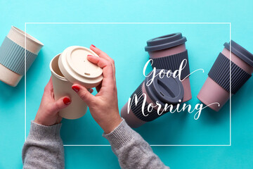 """Text """"Good morning"""" in frame. Assorted bamboo travel reusable coffee or tea cups or mags. Hands open silicon lid. Eco friendly zero waste solution for low impact sustainable lifestyle."""