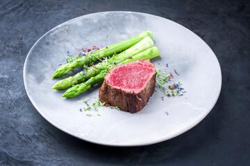Papiers peints Montagne Gegrilltes dry aged Wagyu Filetkopf Medaillon Steak vom Rind natural mit grünen Spargel und Kräuter als closeup auf einem Modern Design Teller mit Textfreiraum