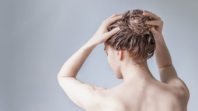 Girl lathers her head with shampoo on a blue background view from the back. Hair care concept