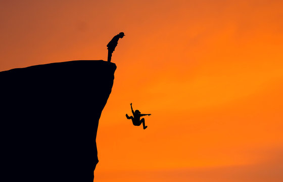 Silhouette Man Looking At Woman Falling From Cliff Against Clear Orange Sky